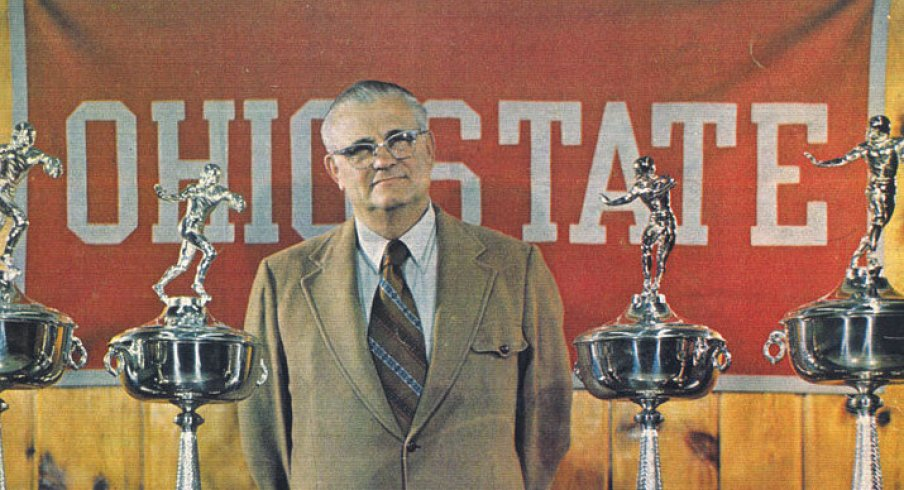 Hayes poses with a small sampling of his hardware for the 1976 Michigan game program cover.