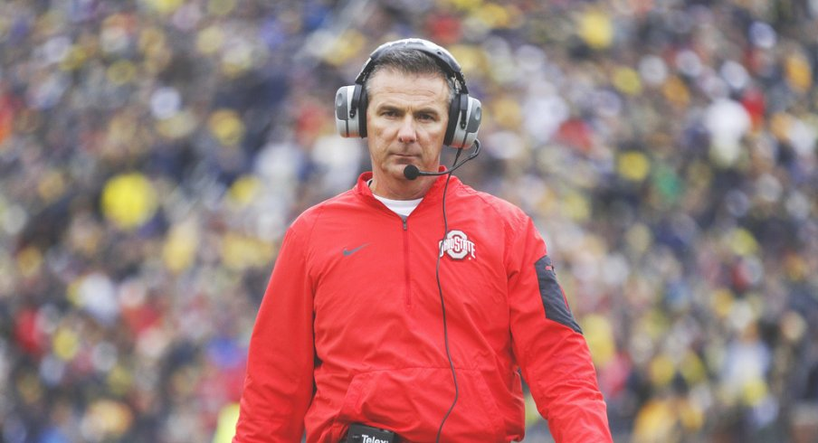 Urban Meyer strolls the sidelines at Michigan.