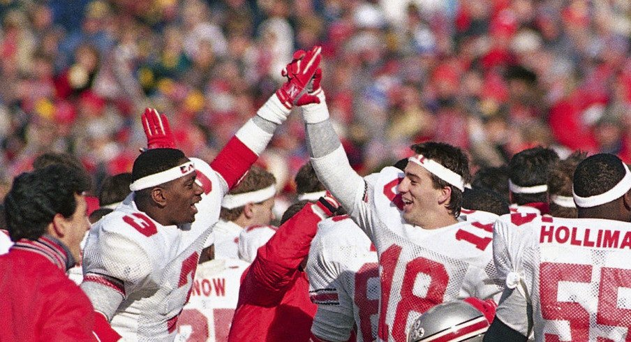"""Ohio State players celebrated after wearing """"Earle"""" headbands and beating Michigan in Earle Bruce's final game in 1987. (Robert Kozloff, Associated Press)"""