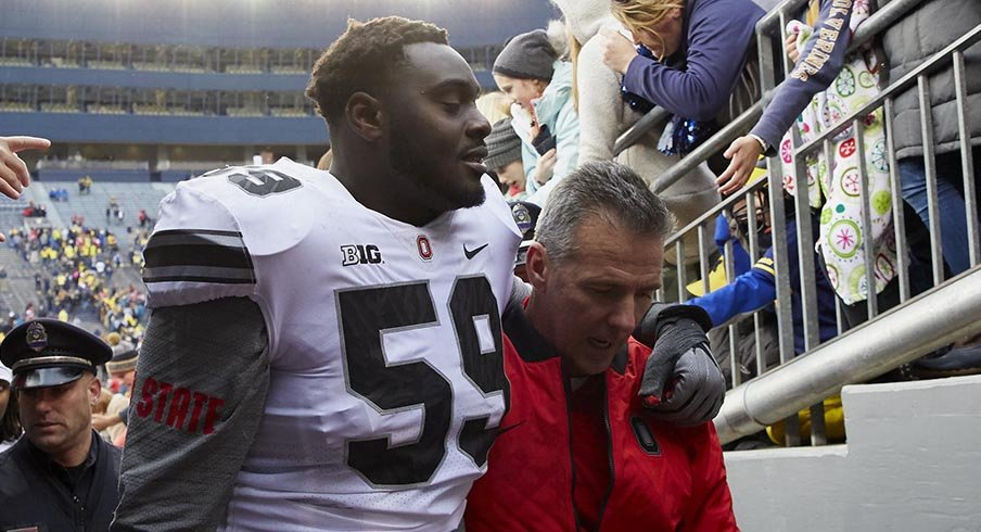 Tyquan Lewis and Urban Meyer exit the field following Ohio State's 31-20 win over Michigan