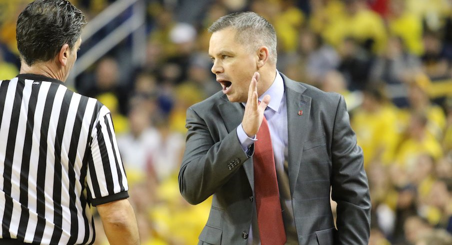 Chris Holtmann talking to official Gene Steratore during Sunday's game at Michigan.