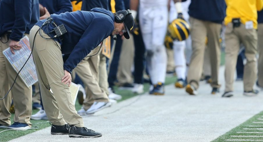 Jim Harbaugh inspects the ground in Ohio Stadium.