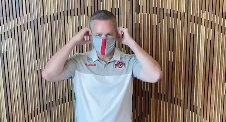Chris Holtmann puts on a mask.
