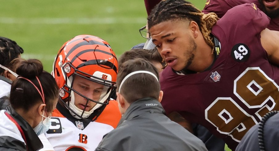 Nov 22, 2020; Landover, Maryland, USA; Cincinnati Bengals quarterback Joe Burrow (9) shakes hands with Washington Football Team defensive end Chase Young (99) prior to being carted off the field after injuring his left knee in the third quarter at FedExField. Mandatory Credit: Geoff Burke-USA TODAY Sports