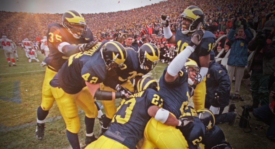 Michigan cornerback Charles Woodson is mobbed by celebrating teammates after his 2nd quarter punt return for a touchdown against Ohio State University on Saturday, Nov 22, at Michigan Stadium in Ann Arbor, MI